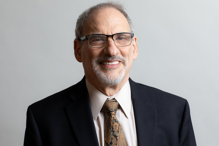 This is a photo of Ed Friedman. Ed is wearing a suit and tie. He has short hair and a goatee. He is wearing glasses. Credit: Jeremy Amar