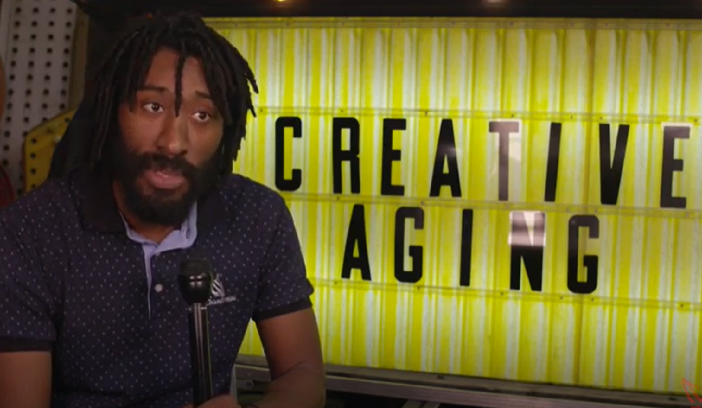 Screenshot of teaching artist, Chase McCuroy infront of a Creative Aging sign.