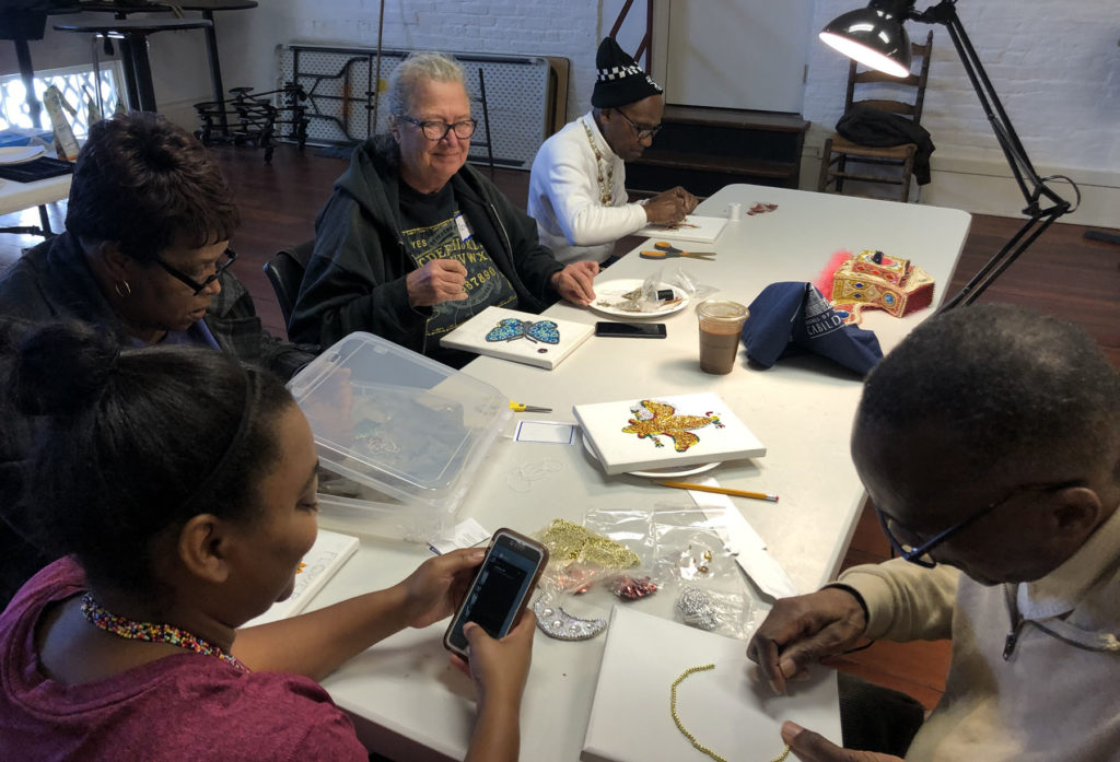 A group of four older adults, black and white, sit at a table and work on beading projects with teaching artist, Big Chief Darryl Montana, at the Louisiana State Museum in New Orleans