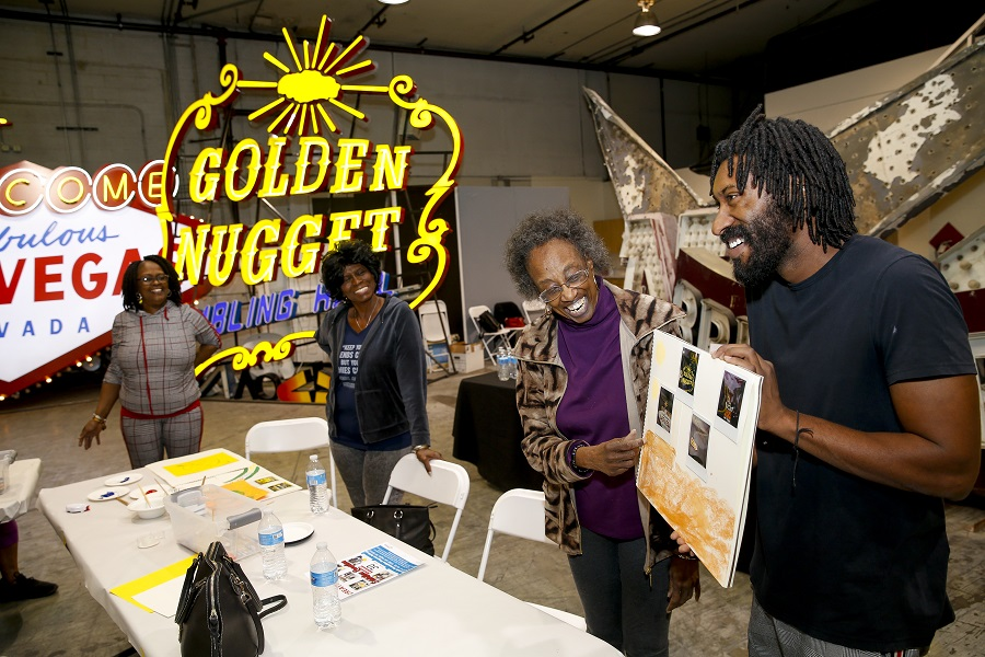 Two older adult participants and a teaching artist smile and admire a finished photography project.