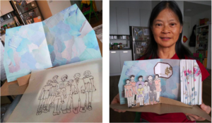 "LaGuardia Senior Center student, Margaret Yuen, sharing her pop-up memory book, ""A Prosperous Family全家福,"" Margaret used materials found around her home to create this pop-up using Spica Wobbe and Karen Oughred's instructional videos. Credit: The Memory Project: Storytelling through Visual Arts, Theater and Puppetry"