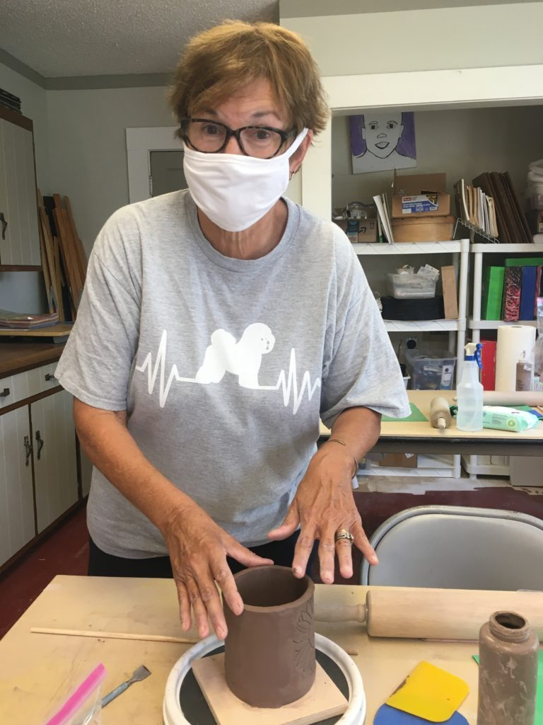 Participant works on pottery in a mask during COVID-19.